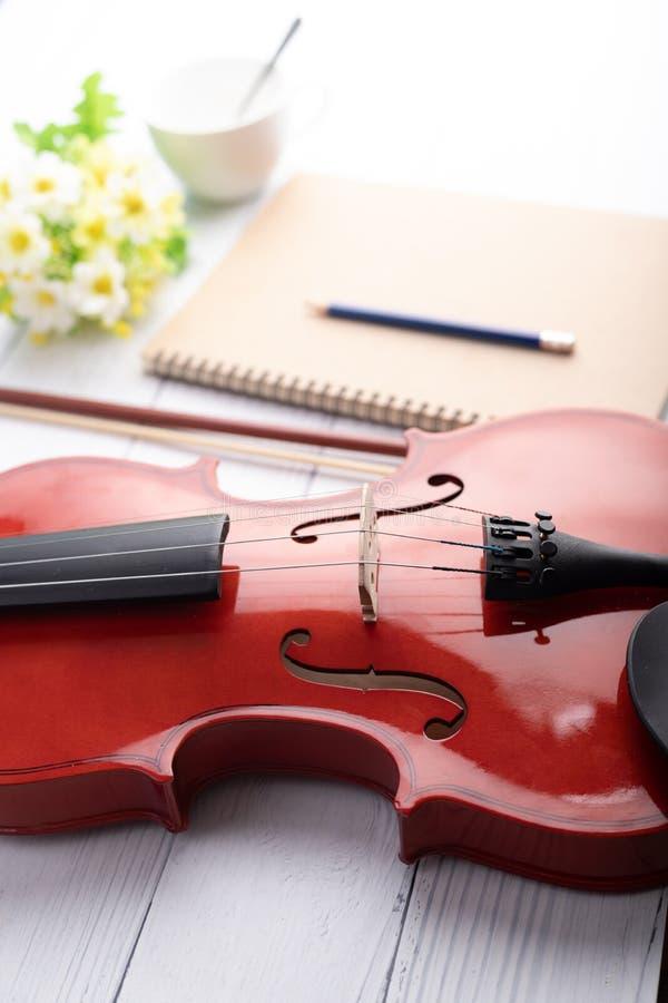 Orchestre tiré en gros plan de violon instrumental et carnet au-dessus de profondeur de foyer choisi en bois blanc de fond de cha photos libres de droits