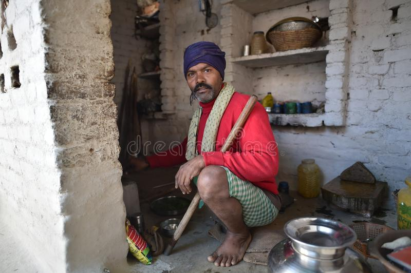Orchha, India, November 28, 2017: Man cooking at home. On the floor stock photo