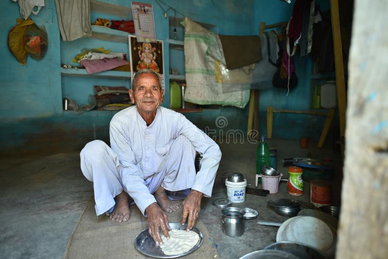 Orchha, India, November 28, 2017: Man cooking at home. On the floor royalty free stock photo