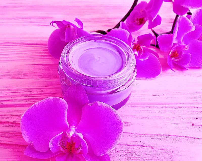 Orchidée naturelle de branche de conteneur de hydrater de produit biologique cosmétique crème d'essence sur un en bois rose photographie stock
