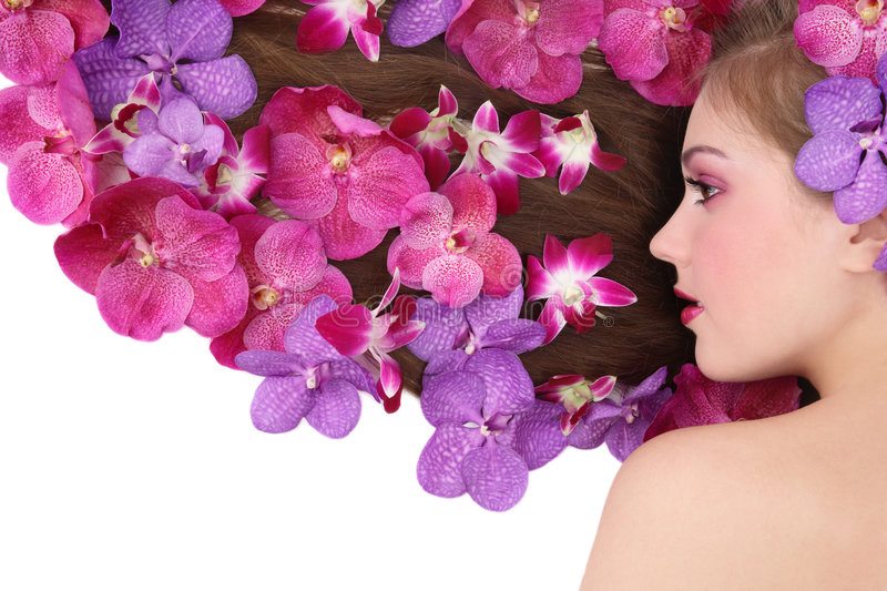 Orchid hairstyle. Beautiful girl lying on white background with orchids in her long hair