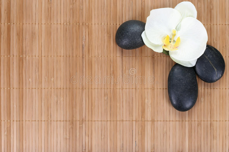 Orchid with zen stones on bamboo background.  stock image