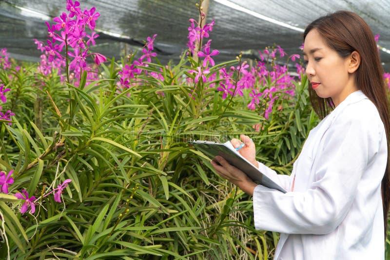 Orchidea botanica di ricerca del ricercatore felice che indossano un cappuccio bianco e la sua mano che tengono una penna e taccu immagine stock libera da diritti