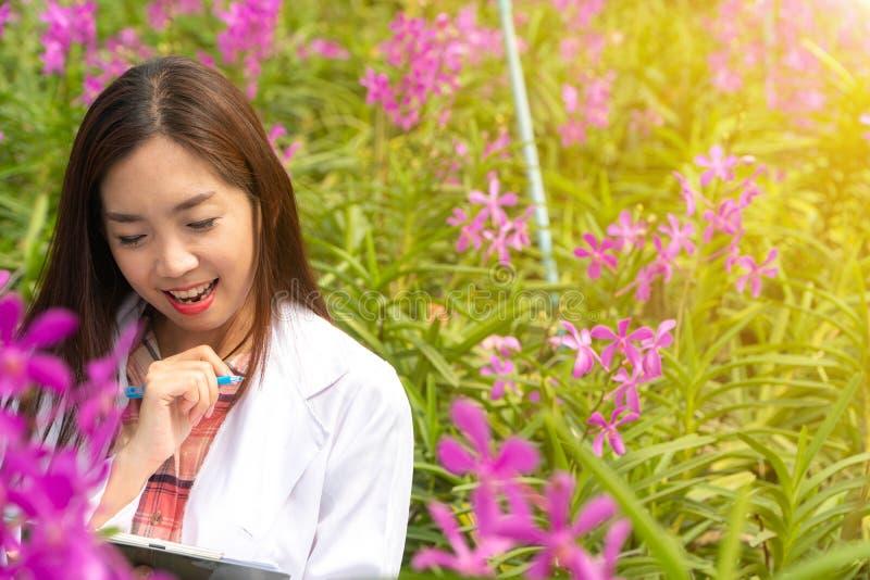 Orchidea botanica di ricerca del ricercatore felice che indossano un cappuccio bianco e la sua mano che tengono una penna e taccu fotografia stock libera da diritti