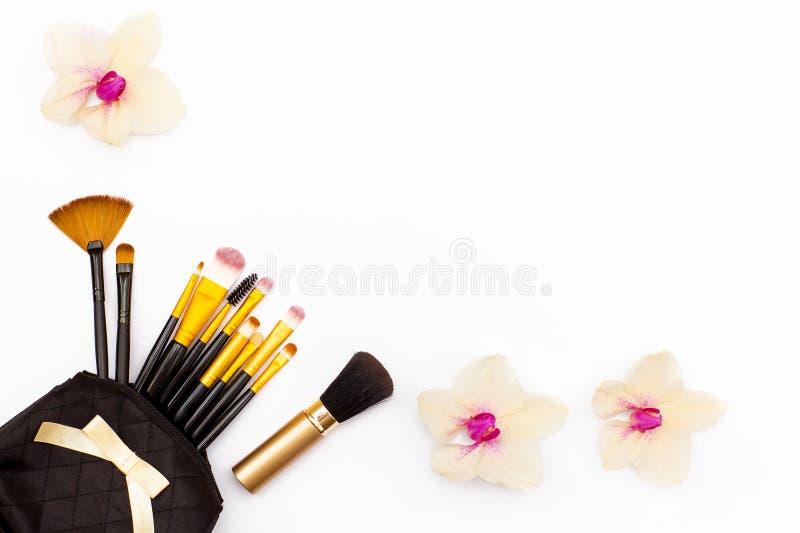 Orchidea delle spazzole di trucco e di pochi fiori su un fondo bianco Concetto di bellezza Disposizione piana immagini stock libere da diritti