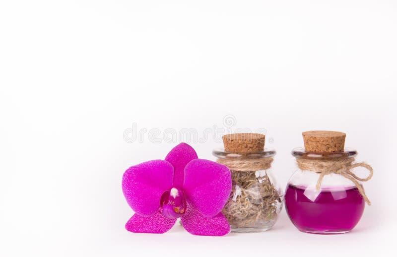 Orchidea rosa e due bottiglie di vetro su un fondo bianco Concetto della stazione termale Bottiglie cosmetiche Cosmetici naturali fotografie stock