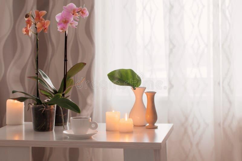 Orchidee, filiżanka, świeczki na stole w pokoju zdjęcia stock