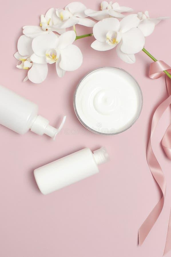 Orchideen, Kerzen und Sch?nheitsprodukte auf dunklem h?lzernem Hintergrund Geöffneter Behälter mit Sahne, kosmetische Flaschenbeh stockfotografie