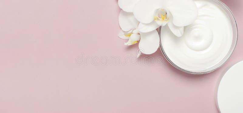 Orchideen, Kerzen und Sch?nheitsprodukte auf dunklem h?lzernem Hintergrund Ge?ffneter Plastikbeh?lter mit Sahne und wei?e Phalaen stockfotos