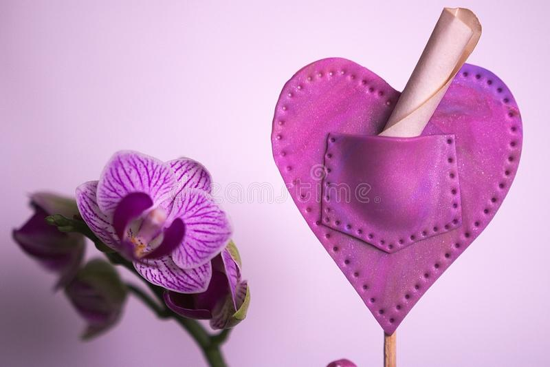 Orchideen- und Polymerherz stockfotografie