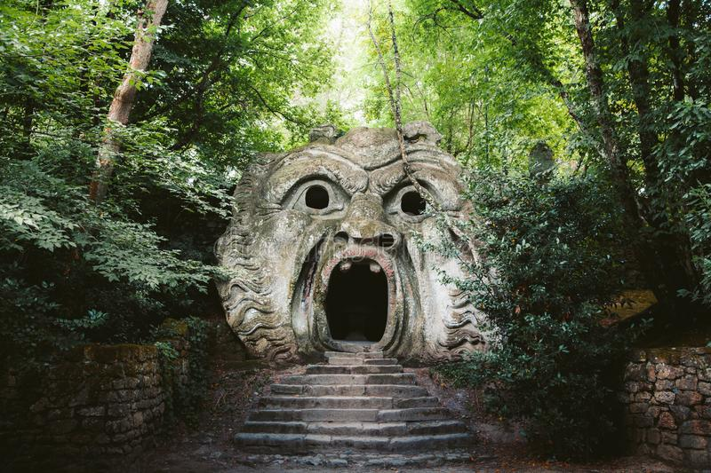 Parco dei Mostri Park of the Monsters in Bomarzo, province of Viterbo, Lazio, Italy. Orcus mouth sculpture at famous Parco dei Mostri Park of the Monsters, also royalty free stock photo