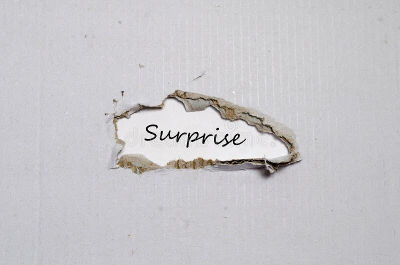 Ordöverraskningen som visas bak sönderrivet papper arkivfoto