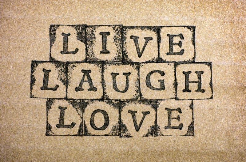 Ord bor, skrattar, förälskelse gör vid svarta alfabetstämplar royaltyfria bilder