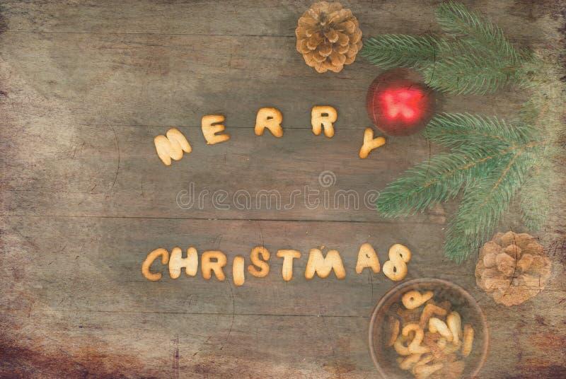 Ord för glad jul som är skriftligt med kexbokstäver på trätabl arkivbild