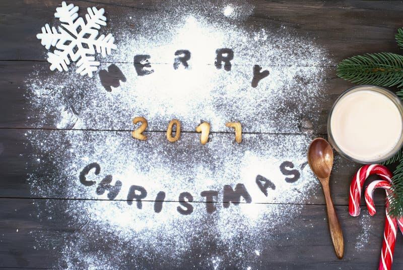 Ord för glad jul som är skriftligt med kexbokstäver på trätabl royaltyfri bild