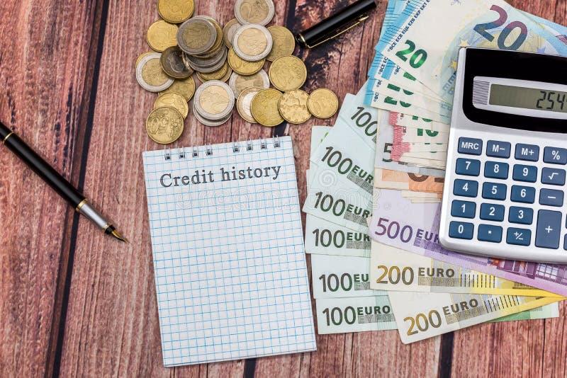 Ord för krediteringshistoria i notepaden med euro, räknemaskin arkivbilder
