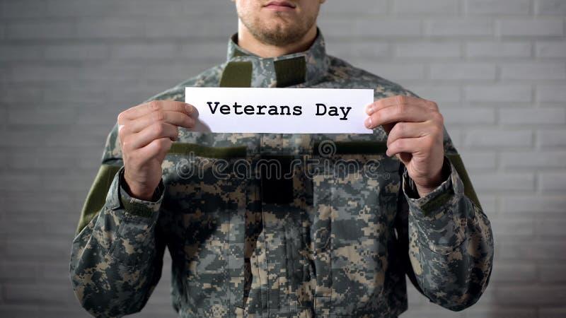 Ord för veterandag som är skriftligt på tecken i manlig soldathänder, tacksamhet och respekt royaltyfri bild