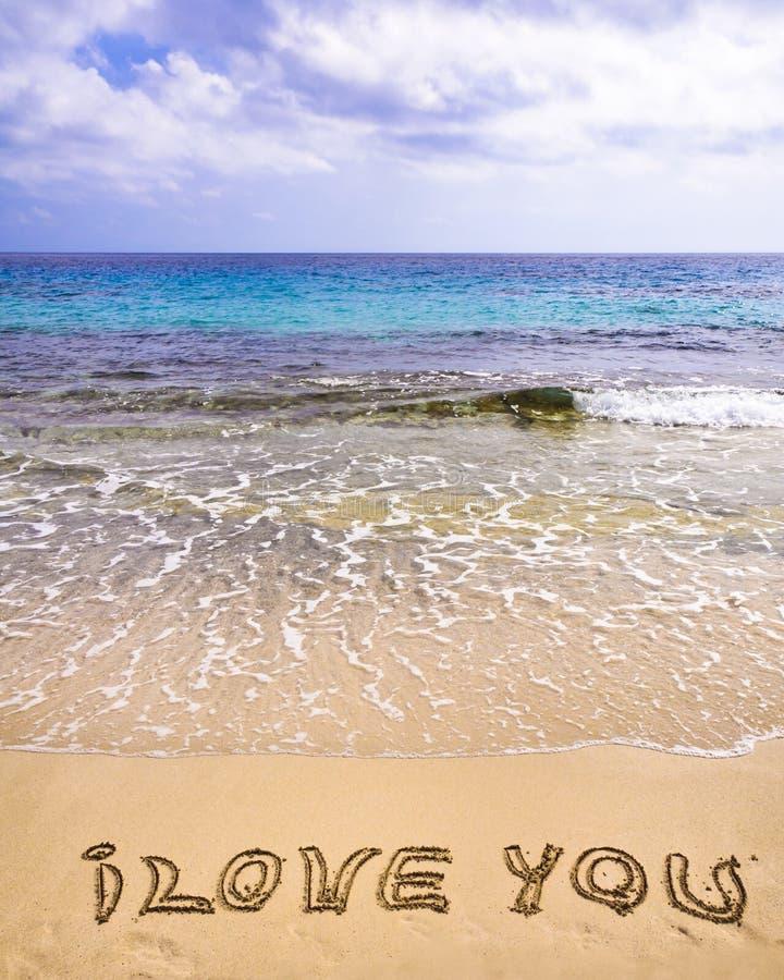 Ord I ÄLSKAR DIG som är skriftlig på sand, med vågor i bakgrund royaltyfri bild