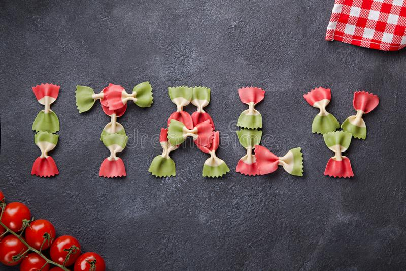 Ord Italien från italiensk flaggafarfallepasta på mörk bakgrund som är horisontal med körsbärsröda tomater och servetten royaltyfri foto