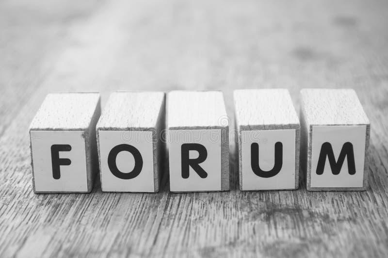 ord på träkuben på träskrivbordbakgrundsbegrepp - forum arkivbild