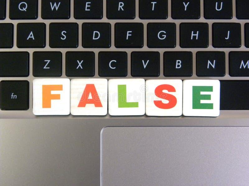 Ord som är falskt på tangentbordbakgrund royaltyfri fotografi