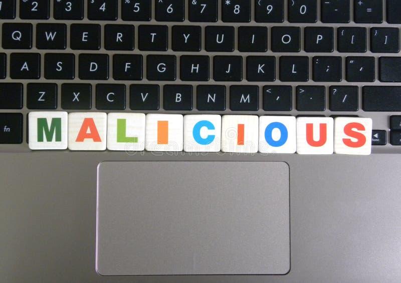 Ord som är ondsint på tangentbordbakgrund royaltyfri bild