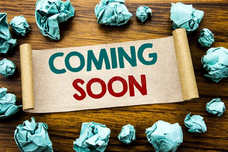 Ord som skriver att komma snart Affärsidé för framtida skriftligt för meddelande på klibbigt anmärkningspapper, träbakgrund med v arkivbild