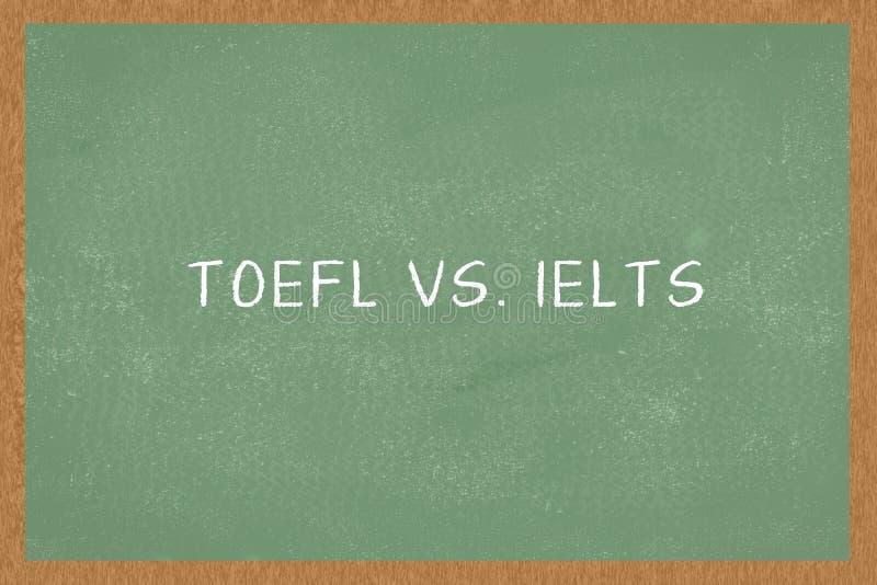 Ord TOEFL vs IELTS grön svart tavlabakgrund Prov av engelska som examina för ett utländskt språk arkivbild
