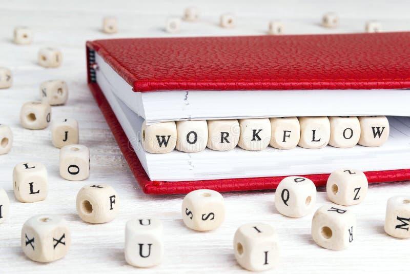 Ordarbetsflöde som är skriftligt i träkvarter i röd anteckningsbok på vit arkivbilder