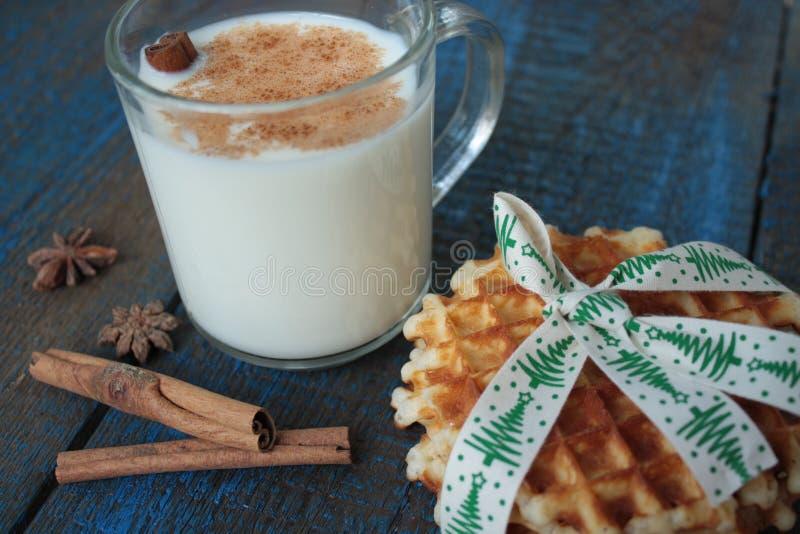 Ordeñe con canela en una taza transparente, se enrolla, las tortas, atadas con la cinta de la Navidad, fotos de archivo