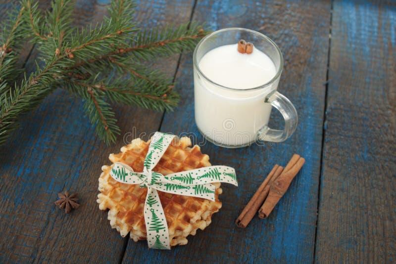 Ordeñe con canela en una taza transparente, se enrolla, las tortas, atadas con la cinta de la Navidad, anís fotos de archivo libres de regalías