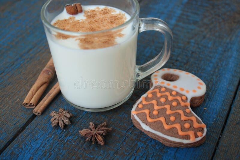 Ordeñe con canela en una taza transparente, se enrolla, las tortas, atadas con la cinta de la Navidad, anís foto de archivo