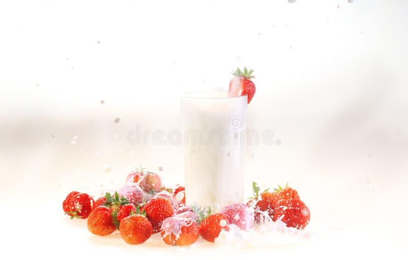 Ordeñe en un vidrio transparente y una fresa en un backgrou blanco imagen de archivo