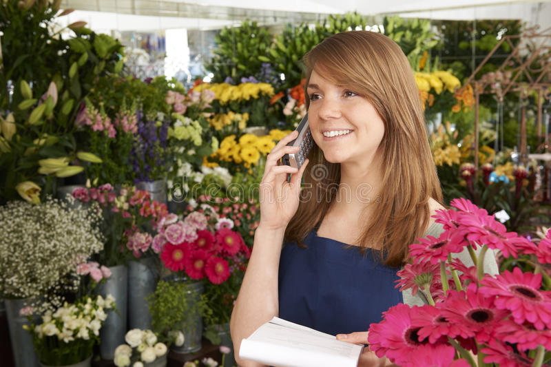 Ordem de In Shop Taking do florista sobre o telefone na loja imagem de stock royalty free