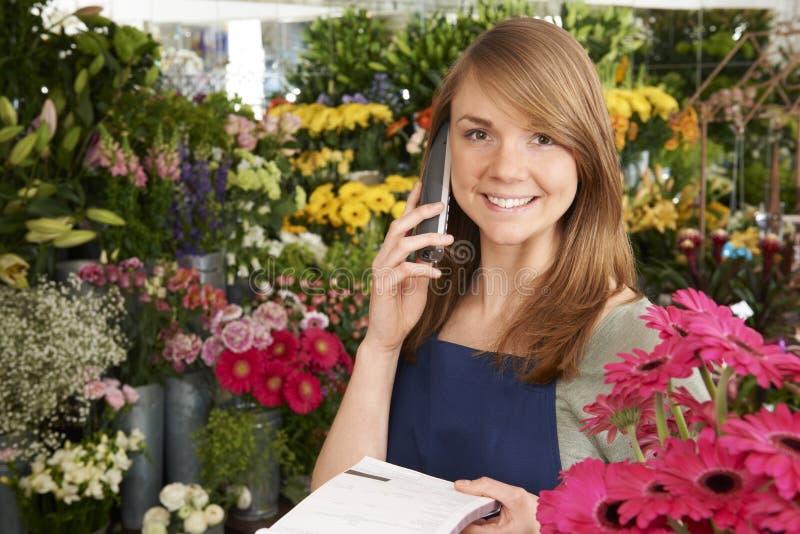Ordem de In Shop Taking do florista sobre o telefone na loja foto de stock royalty free