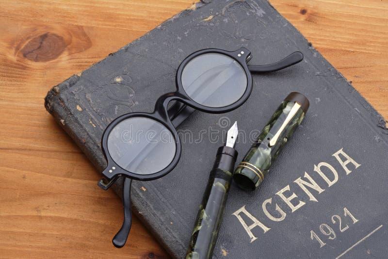 Orden del día, pluma y lentes del vintage fotografía de archivo