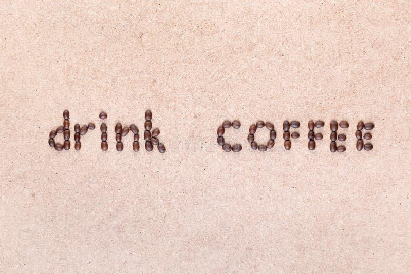 Orden dricker kaffe som ?r skriftligt med kaffeb?nor som skjutas fr?n ?ver royaltyfri bild