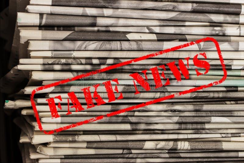 Orden fejkar nyheterna i röd text på tidningar arkivfoton