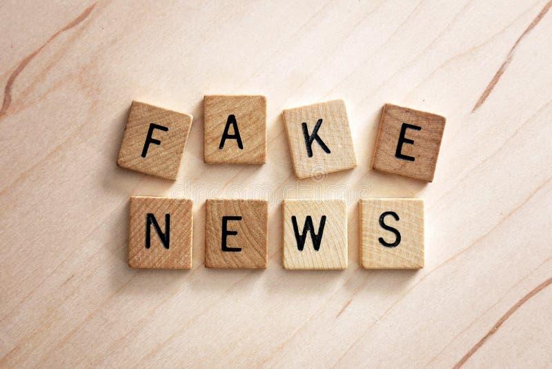 Orden fejkar nyheterna stavas ut i träbokstavstegelplattor på en ljus träbakgrund royaltyfria bilder