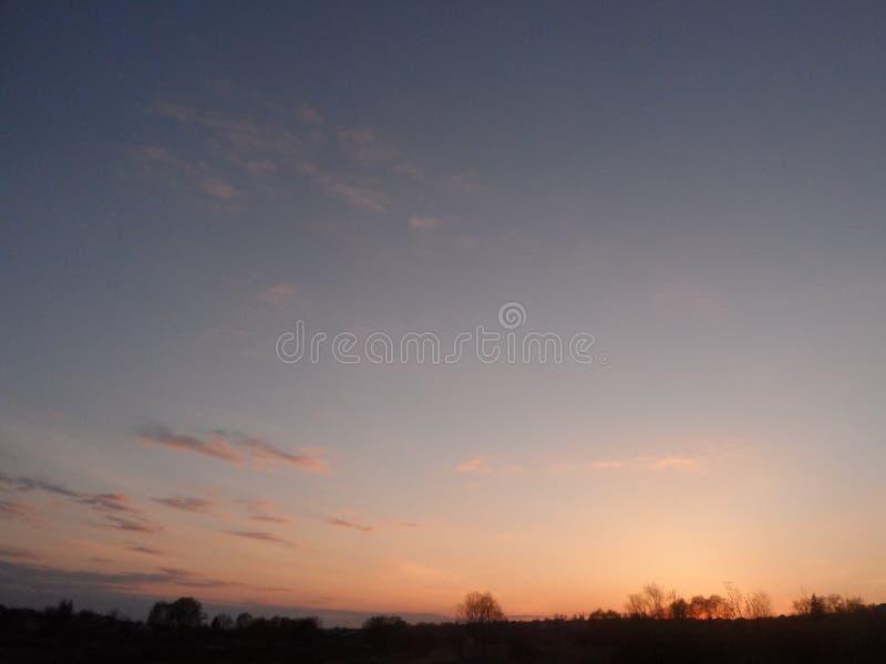 Orden hermosa en el horizonte con las nubes y el bosque anaranjados en el horizonte foto de archivo