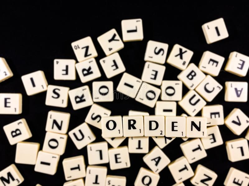 Orden word spelled with letter tiles in black background. Orden orden in spanish word written with white letter tiles over a mess of other letters stock photo