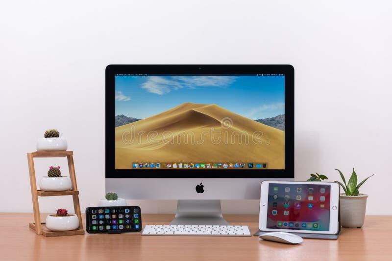 Ordenador de IMac, teclado, ratón mágico, iPhone X, iPad mini, florero de la planta y potes del cactus en la tabla de madera fotos de archivo