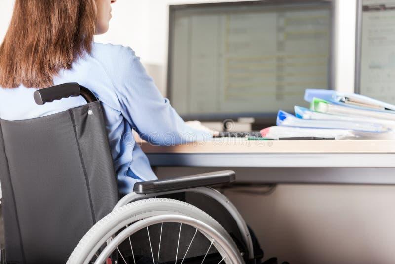 Ordenador de trabajo del escritorio de oficina de la silla de ruedas de la mujer que se sienta inválida o discapacitada imagen de archivo