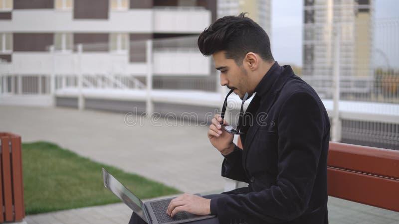 Ordenador de trabajo joven del ablet del tiempo largo del hombre de negocios y al aire libre cansado fotografía de archivo