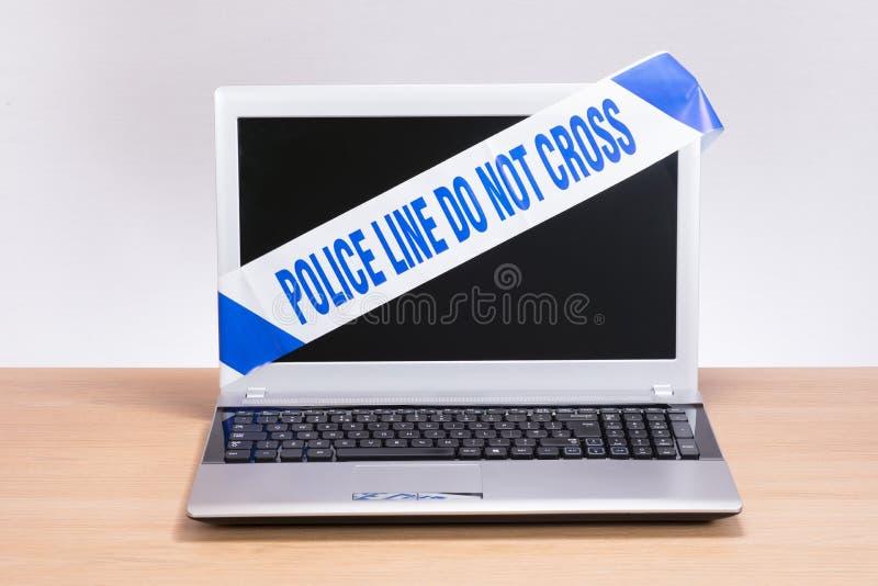 Ordenador portátil abierto de la oficina con la cinta de la escena del crimen de la policía imagen de archivo libre de regalías