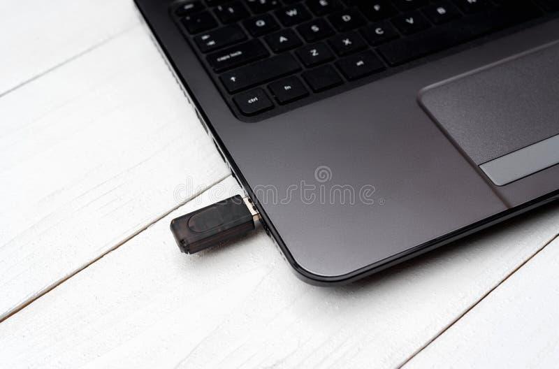Ordenador portátil abierto gris con memoria USB en el conector fotos de archivo libres de regalías