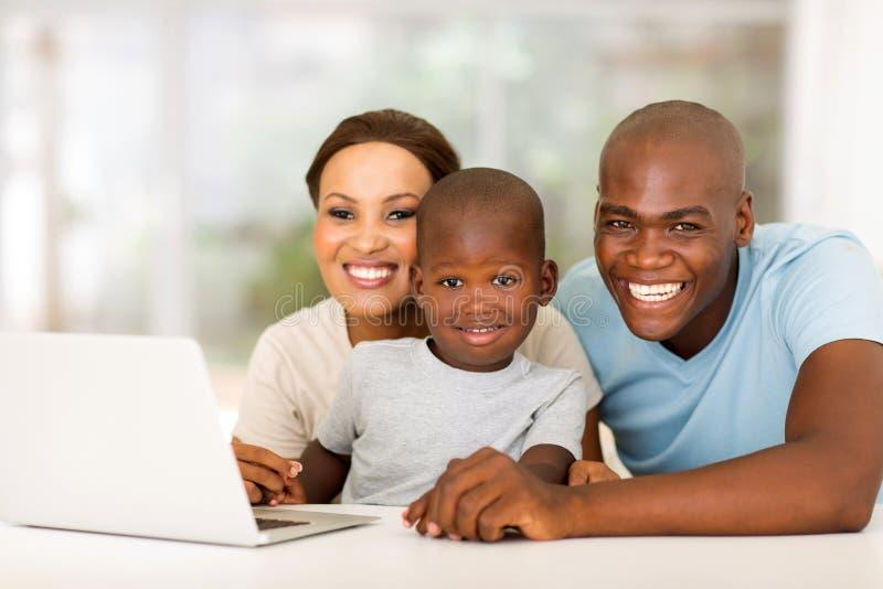 Ordenador portátil africano de la familia imagenes de archivo