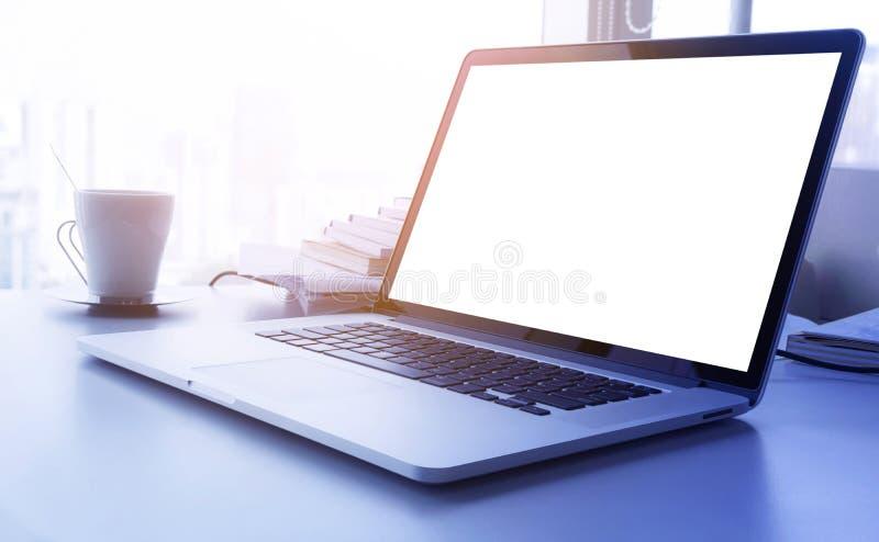 Ordenador portátil amarillo claro del efecto del filtro con la pantalla en blanco en oficina de la tabla del escritorio imagen de archivo