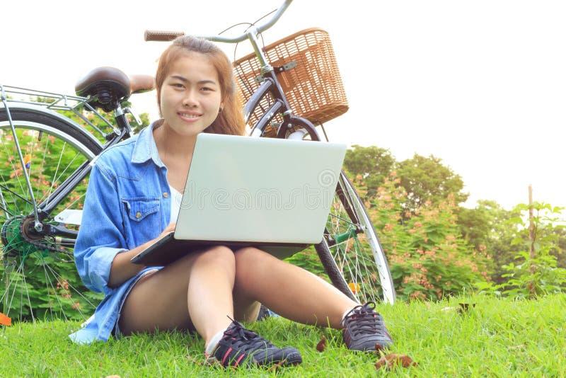 Ordenador portátil asiático en el parque, Asia del uso de la mujer del retrato fotografía de archivo