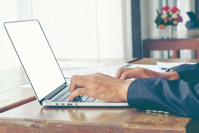Ordenador portátil blanco de la pantalla del uso del hombre de negocios en la tabla de madera fotografía de archivo